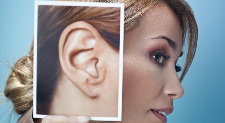 mid adult business woman holding photo of her ear on blue background. Vertical shape, side view, head and shoulders, copy space